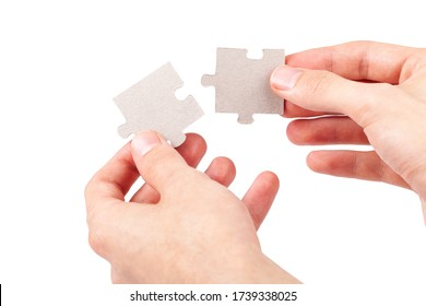 Hands putting together, connecting two matching blank jigsaw puzzle pieces, joining corresponding fitting parts, elements isolated on white, cut out. Solution, problem solving, unity abstract concept