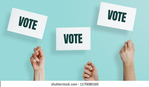 Hands raise the white flags with the word VOTE up. The concept of voting, making choices. Presidential and parliamentary elections. Calling for voting, democracy.