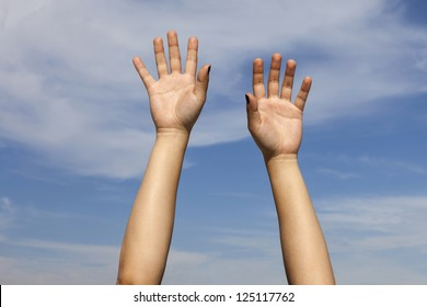Hands raised against the sky. A pair of hands, lit by the sun, raised above somebody's head against a slightly cloudy blue sky. Hands belong to a 23 year old female.