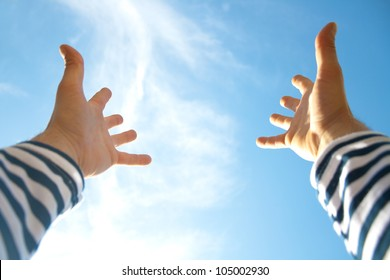 Hands raised up in air across blue sky