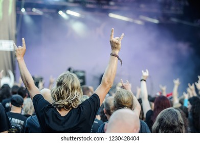 Hands raised showing a heavy metal rock sign, devil horns