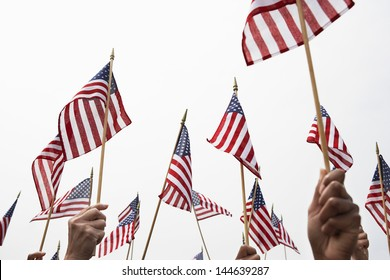 Hands raising American flags against clear sky
