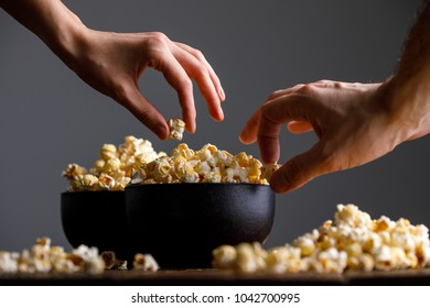 Hands reach for a bowl with tasty popcorn. Still-life on a wooden background.
