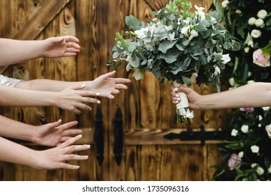 hands reach for a wedding bouquet,female hands try to catch the bride's wedding bouquet,the end of the wedding day,beautiful wedding bouquet made by florists,gorgeous flower bouquet on wooden