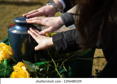 Hands reaching for a burial urn, in a bright outdoor funeral scene, with space for text on the right