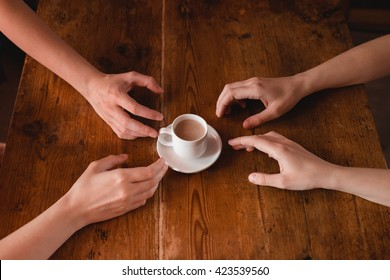 Hands reaching for coffee. Lifestyle image with vintage colors.