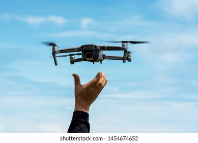 Hands reaching for drone against blue sky