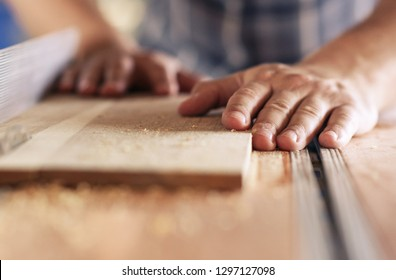 Hands of a real woodworker sawing a piece of wood with a table saw in woodworking studio