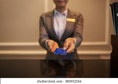 Hands of receptionist giving smart card to you