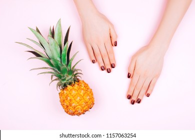 Hands with red manicure on pink background with pineapple. Summer and tropical concept.