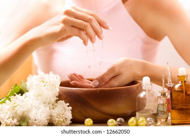 Hands relaxing in bowl of water with rose petals. French manicure.
