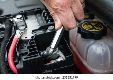 Hands repairing a car engine with a wrench