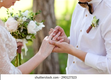 Hands with rings Groom putting golden ring on bride's finger during wedding ceremony