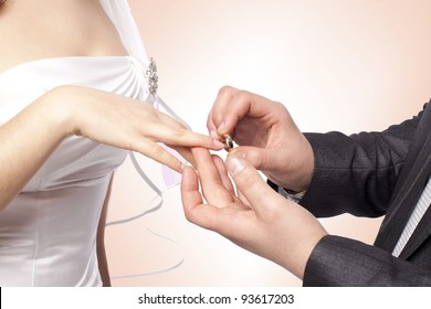 Hands with rings Groom putting golden ring on bride's finger during wedding ceremony Loving couple closeup in studio isolated portrait on white background