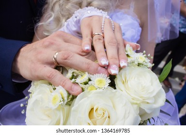 Hands with rings on the fingers of the bride and groom on the background of a wedding bouquet with big white roses.