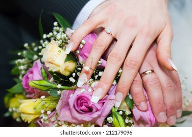Hands with rings on wedding bouquet