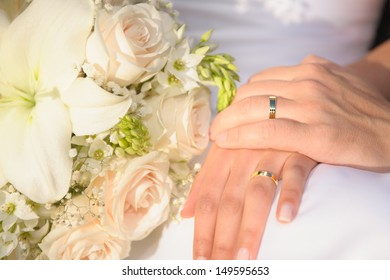 Hands and rings on white dress and wedding bouquet