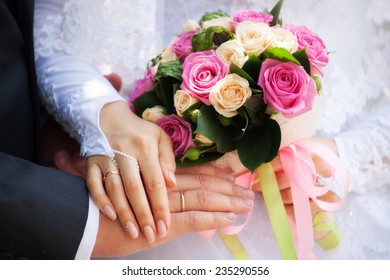 Hands, rings and wedding bouquet