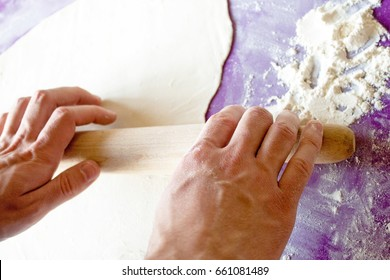 Hands rolling dough with a rolling pin