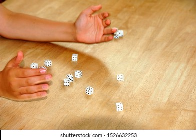 Hands rolling fourteen dice on a wooden table