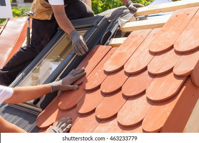 Hands of roofer laying tile on the roof with mansard windows. Installing natural red tile.