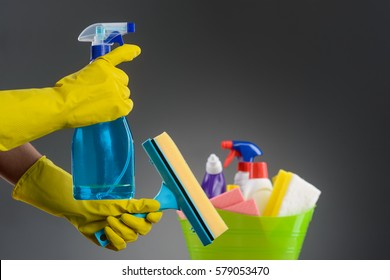 Hands in rubber gloves holding a spray and a window cleaning brush, close-up. Container with liquid disinfectants, a surface cleaning spray, rags and a sponge, blurred. Neutral background.