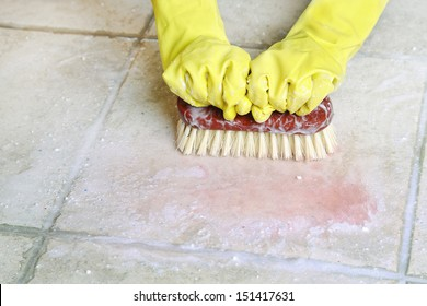 hands in rubber gloves scrubbing the floor