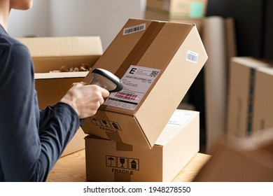 Hands scanning barcode on delivery parcel. Worker scan barcode of cardboard packages before delivery at storage. Woman working in factory warehouse scanning labels on the boxes with barcode scanner.