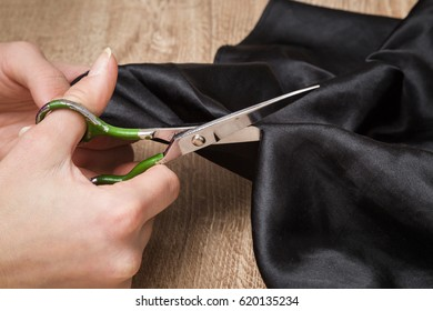Hands with a scissors cuts a cloth. Sewing clothes. Handmade. Womanly hobby.