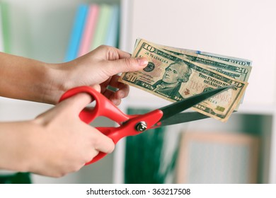 Hands with scissors cutting dollar banknotes, on blurred interior background