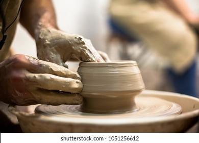 Hands sculpt new utensil on a pottery wheel