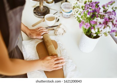 Hands sculpts a cup from clay pot. Woman working on the potter's wheel. Workshop on modeling on the potter's wheel. Handmade consept.