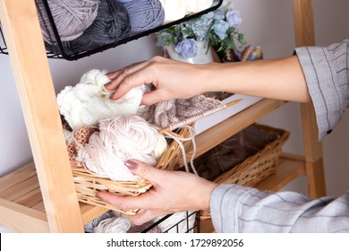 Hands of a seamstress or craftswoman take a container with yarn in blue, white and brown shades standing on a shelf with sewing accessories. Concept of manufacture of knitted clothes to order