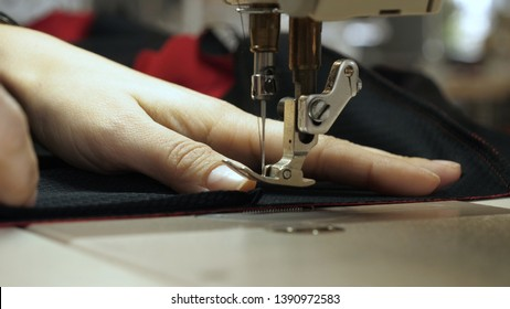 Hands of seamstress sewing with a professional machine, embroiders (sews) on red fabric using both sides of the material. Concept of: Factory, Home, At Work, Professionals.