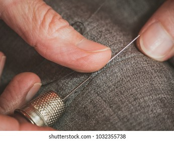 hands of a seamstress who sews, with basting, a jacket of high Italian tailoring
