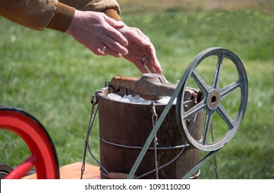 hands are seen adding ice to an old fashioned ice cream maker that is pulley and gas driven to mix up the dessert