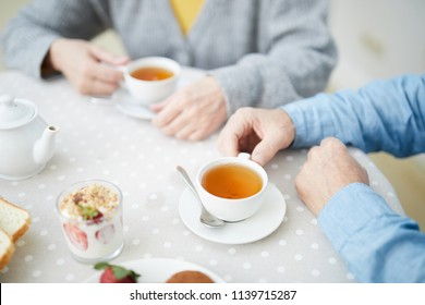 Hands of senior couple by table with cups of drinks, strawberry dessert in glass and white porcelain teapot during tea time