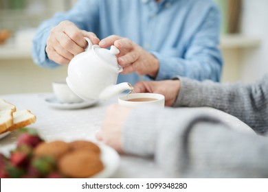 Hands of senior man with white china teapot pouring tea into cup of his wife