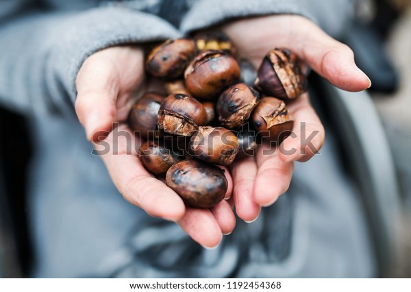 冬に戸外で焼いた栗を持つ老女の手。