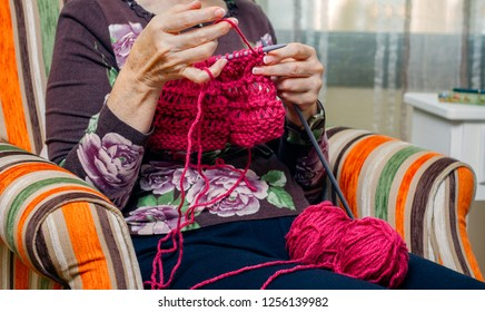 Hands of senior woman knitting a wool sweater at home