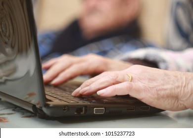 Hands of senior woman typing on laptop