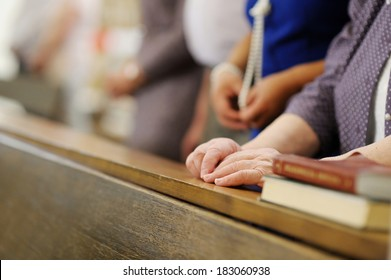 Hands of a senior woman while praying in a church