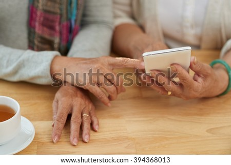 Hands of senior women using smartphone