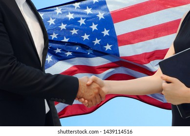 Hands shaking on background USA flag with blue sky,US memorial day.