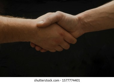 Hands shaking on the black background, Strong man hands. Del and congrats.