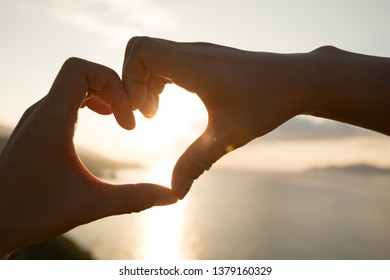 Hands in the shape of heart against the sunset over the sea.