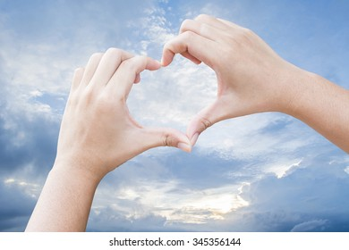 hands in the shape of heart with sky background