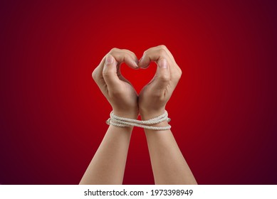 Hands in the shape of a heart tied with rope. Concept of the love of codependency