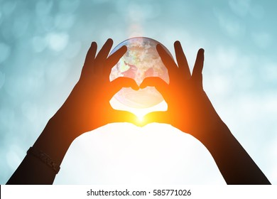 Hands in shape of love heart. Female door hands in the form of heart against the earth and blue blurred pass sun flare. Healthcare and Valentine's day concept. Elements of this image furnished by NASA
