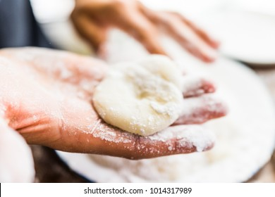 Hands shaping piece of mochi sticky glutinous rice cake dusted with starch flour to make dessert